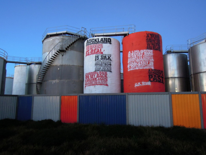 Colorful quotations painted onto the side of cylindrical tanks