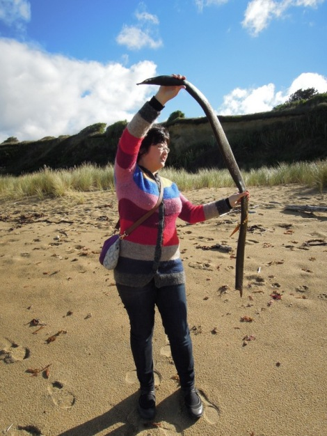 Lisa playing with a big piece of kelp (?) in New Zealand