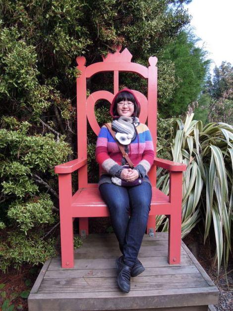 Lisa on a big chair, gardens, Larnach Castle, New Zealand
