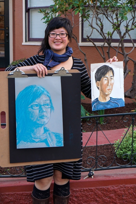 Woman holding two portraits