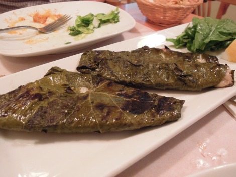 Grilled fish in grape leaves