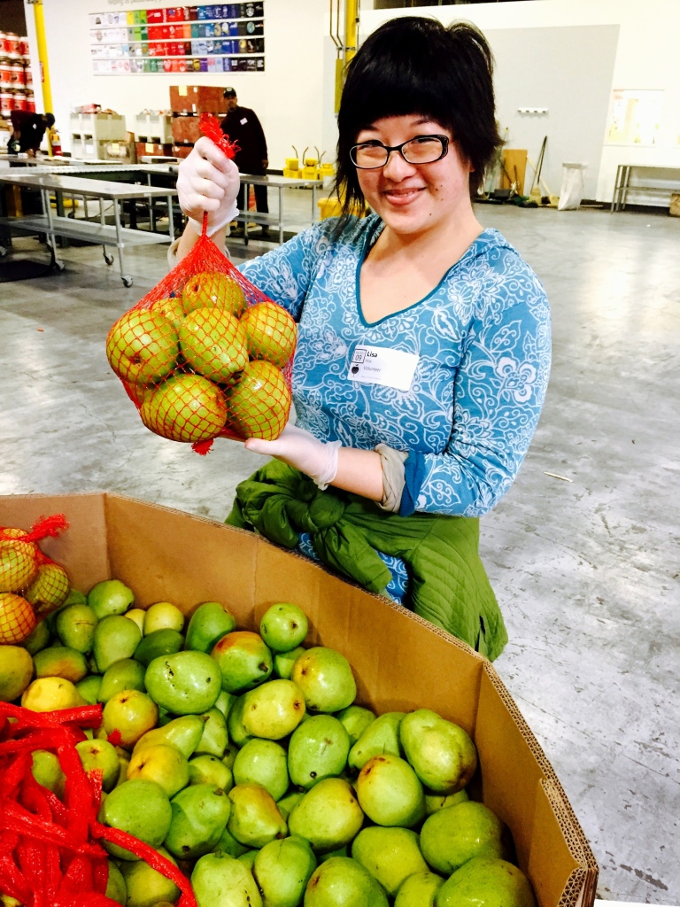 Lisa with a mesh bag of pears at the Alameda County Community Food Bank