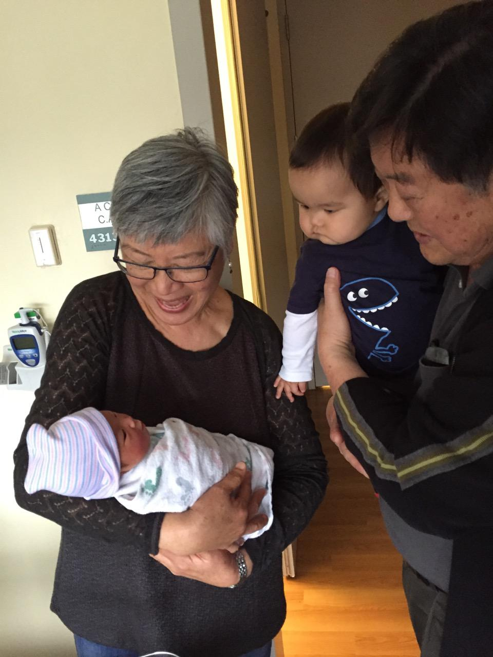 Newborn baby meeting her grandparents and cousin