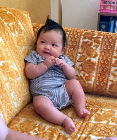 Three-month-old Ada smiles from a vintage couch