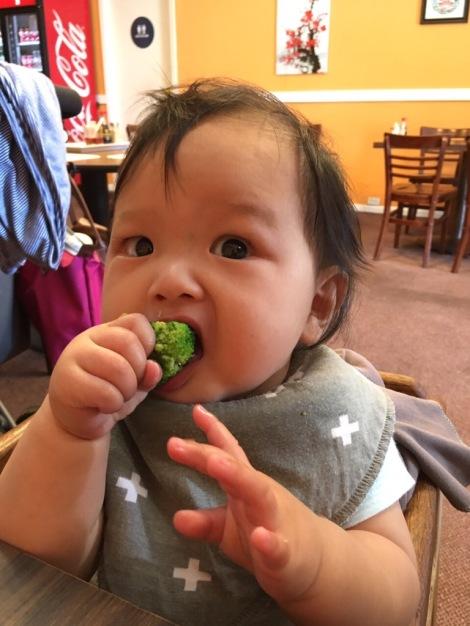 baby Ada eating broccoli