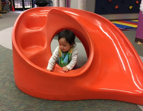 9-month-old Ada playing in an orange play structure