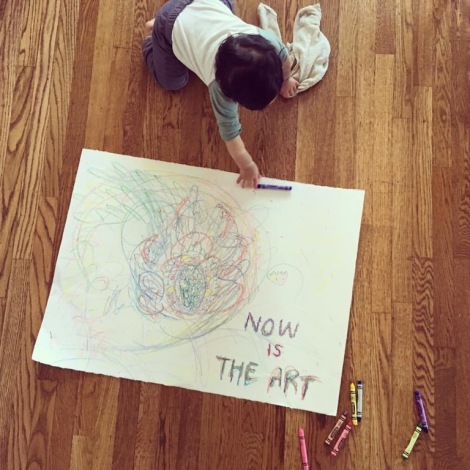 Baby with crayons on a large piece of paper with drawings and the words, NOW IS THE ART
