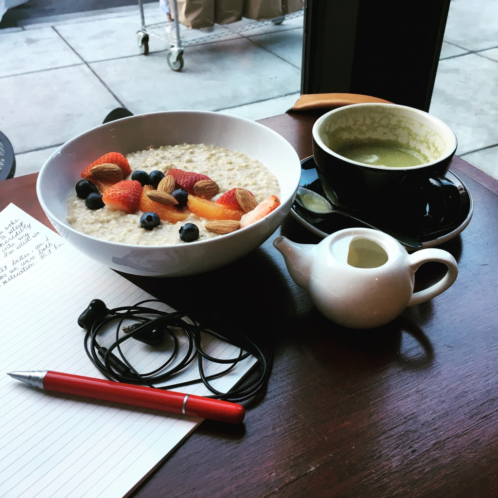 Matcha latte, oatmeal with fruit, earbuds, pen, journal
