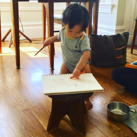 14-month-old Ada standing and drawing with a crayon and a pencil