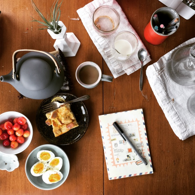 Aerial view of a journal and pen surrounded by tea service and breakfast items