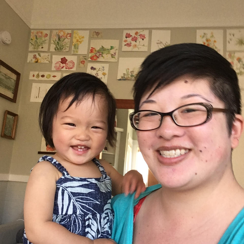 Lisa and 15-month-old Ada, laughing together with Lisa's watercolors hanging on the wall in the background