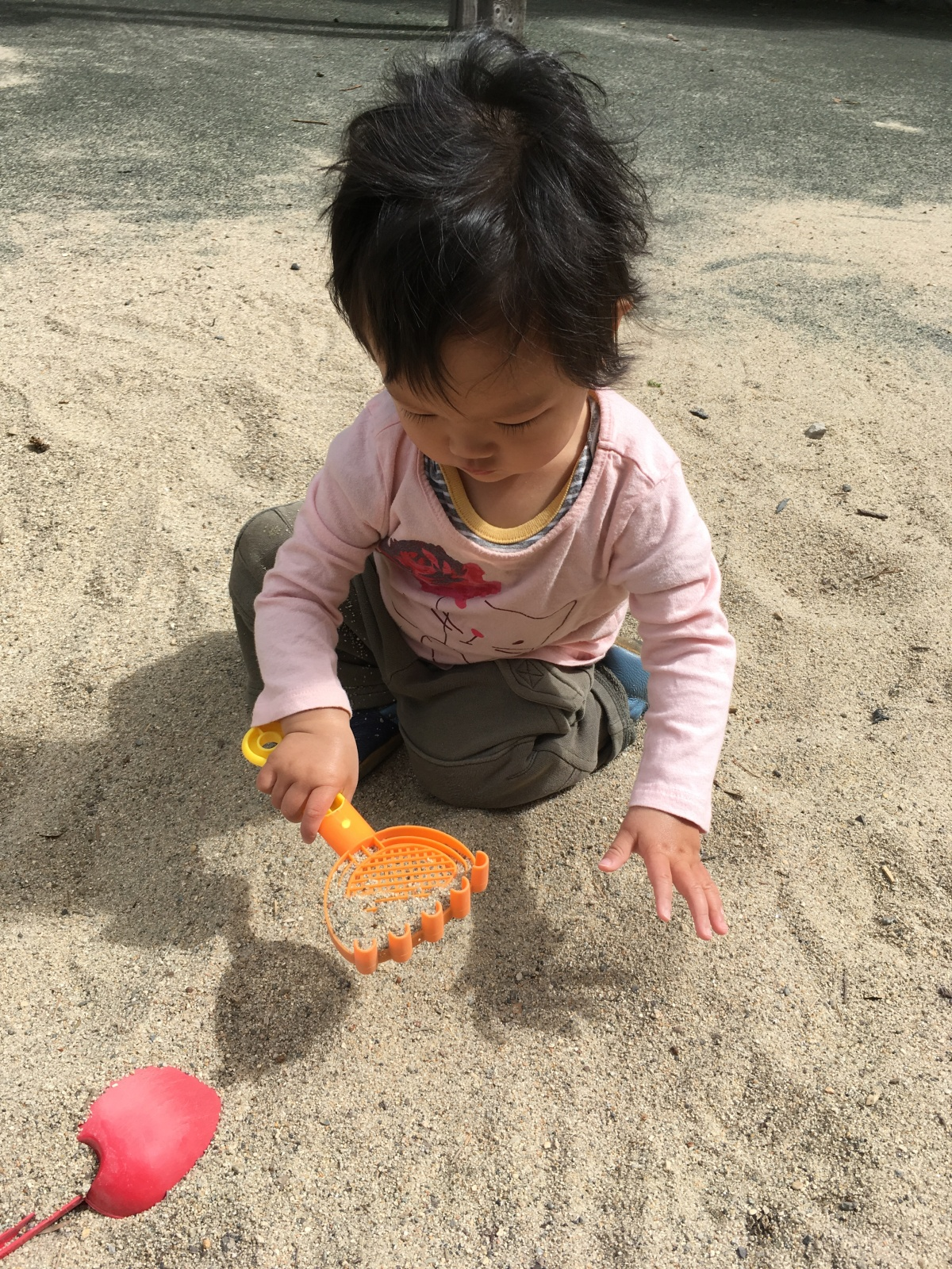 15-month-old Ada, wearing a pink shirt, plays in the sand with an orange rake