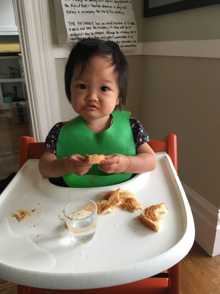 15-month-old Ada eating bread and peanut butter