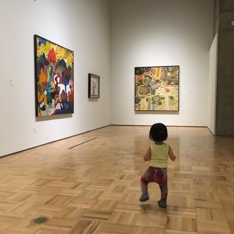 15-month-old Ada walking through the Roy De Forest exhibition at the Oakland Museum
