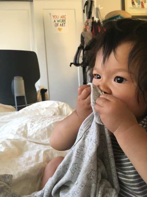 16-month-old Ada holding a onesie to her face