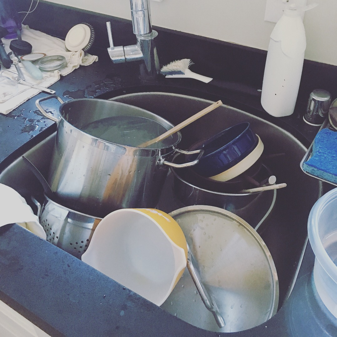 A deep stainless-steel sink filled up with dirty dishes and pots