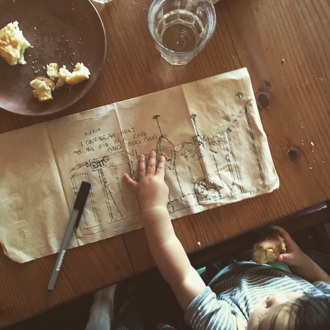 A fineliner drawing on a brown paper napkin, on a table in front of a toddler, whose hand is on it
