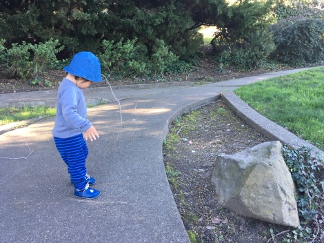 Toddler wearing a hat and lifting up a long thin stick