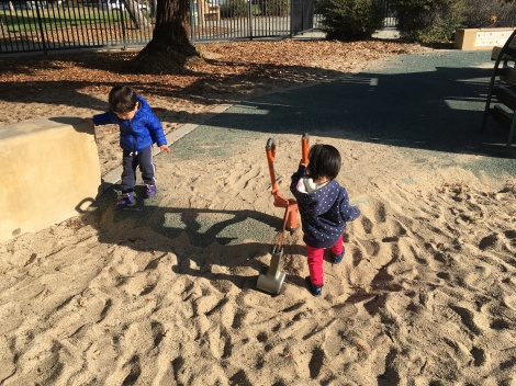 Two toddlers in the sand pit at a playground