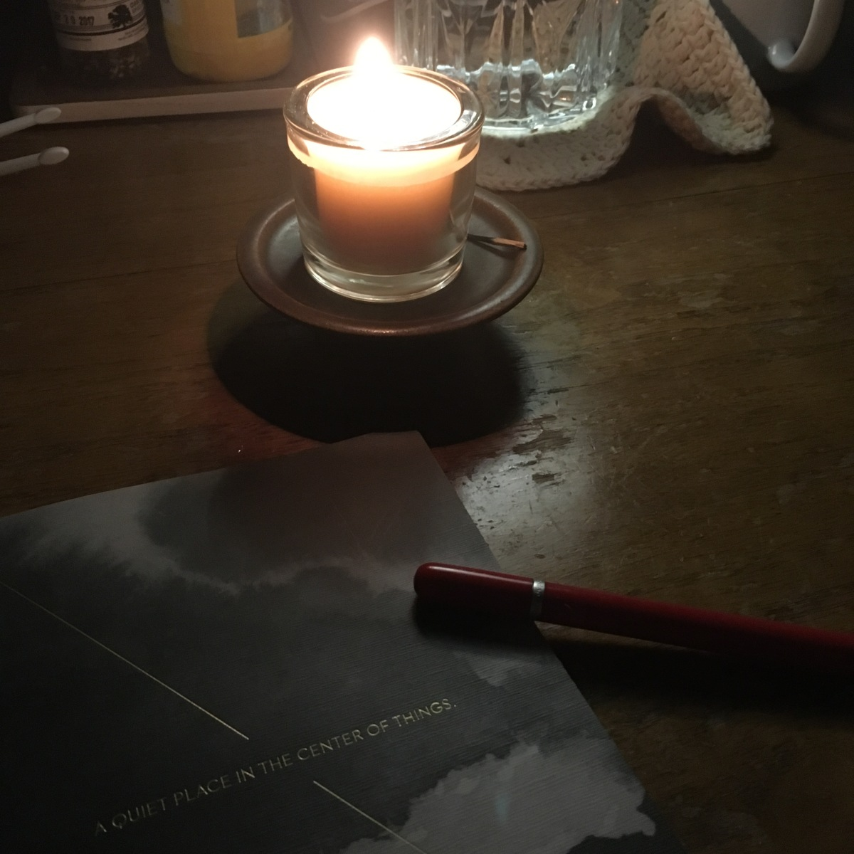 A lit candle at night, with a journal and pen nearby