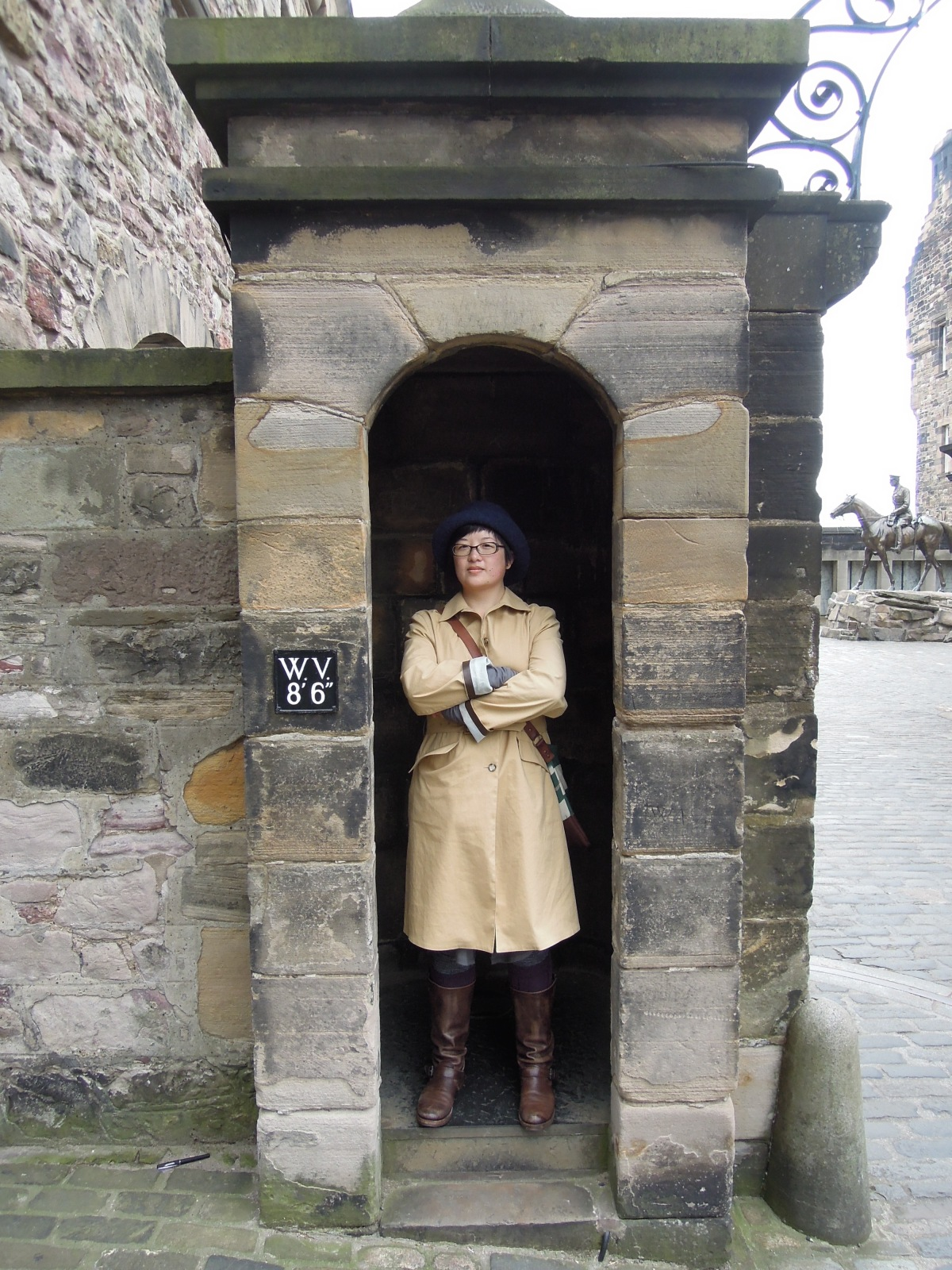 Lisa standing with arms crossed in a guard booth at Edinburgh Castle