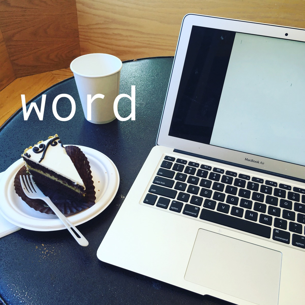 "The word ""word"" imposed over a photo of a laptop open to a blank document, with a coffee cup and a slice of cake next to it"