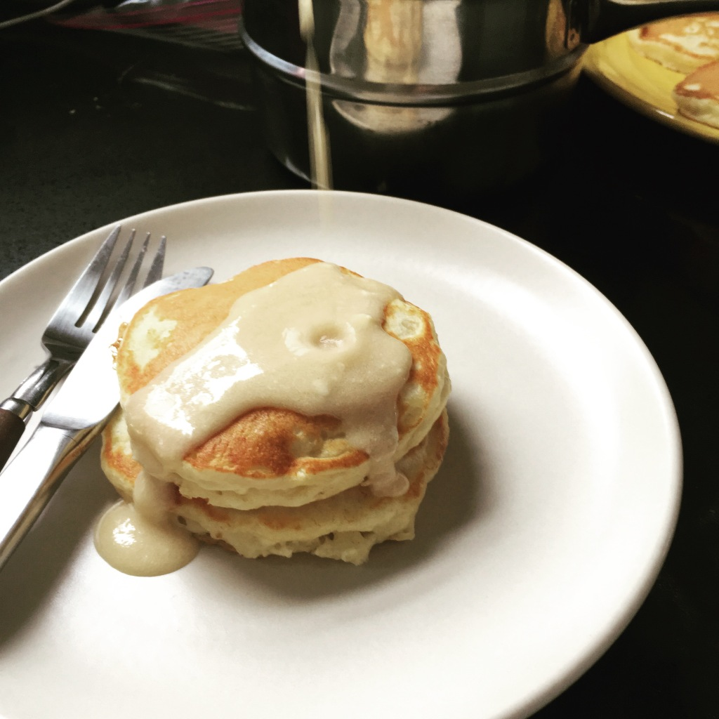Short stack of pancakes with sauce being drizzled on