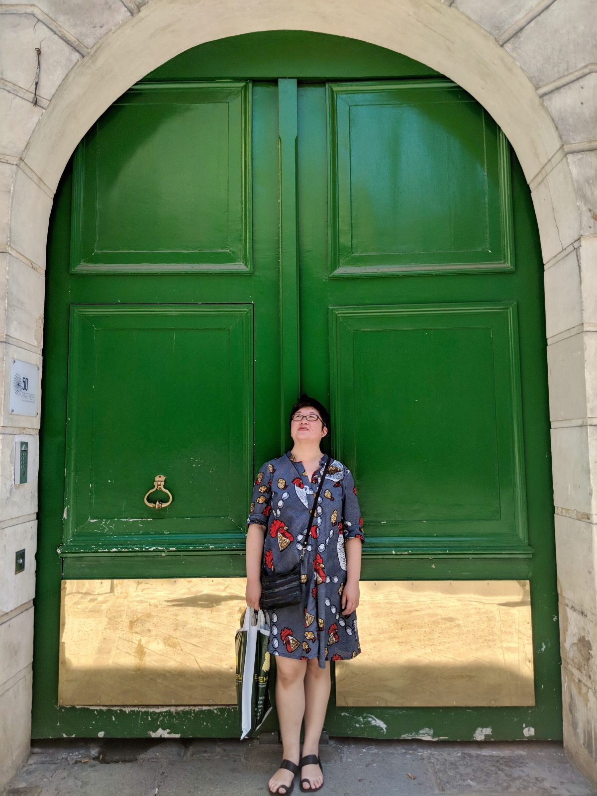 Lisa in front of an arched green door, Paris