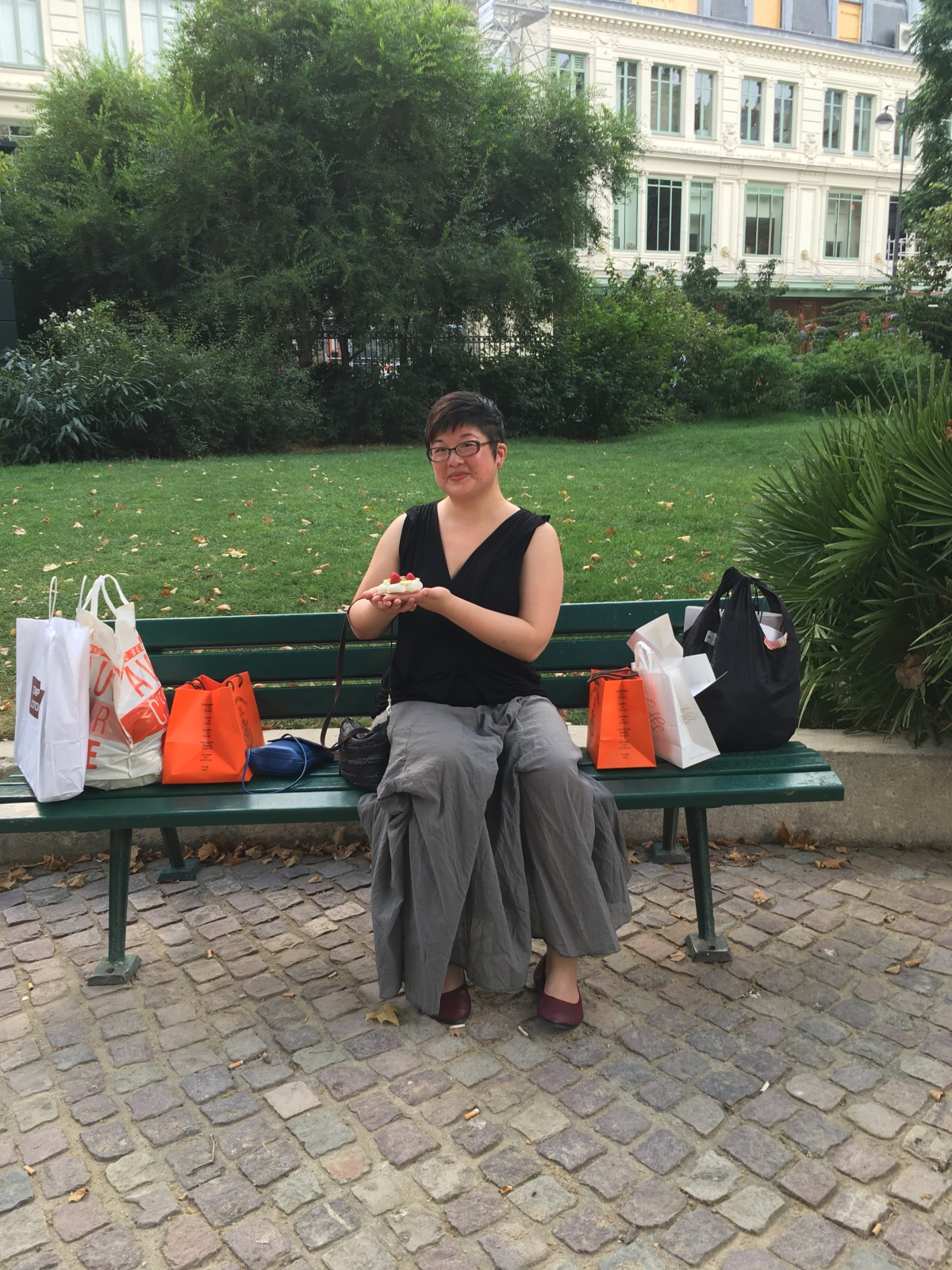 Lisa on a park bench surrounded by shopping bags