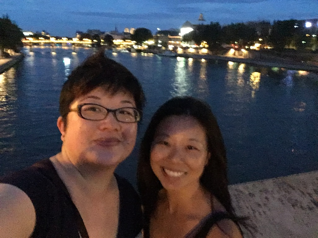 Two Asian women pose for a selfie on the Seine at dusk