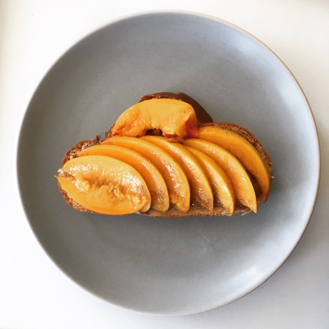 Sliced yellow peaches and almond butter on a slice of challah