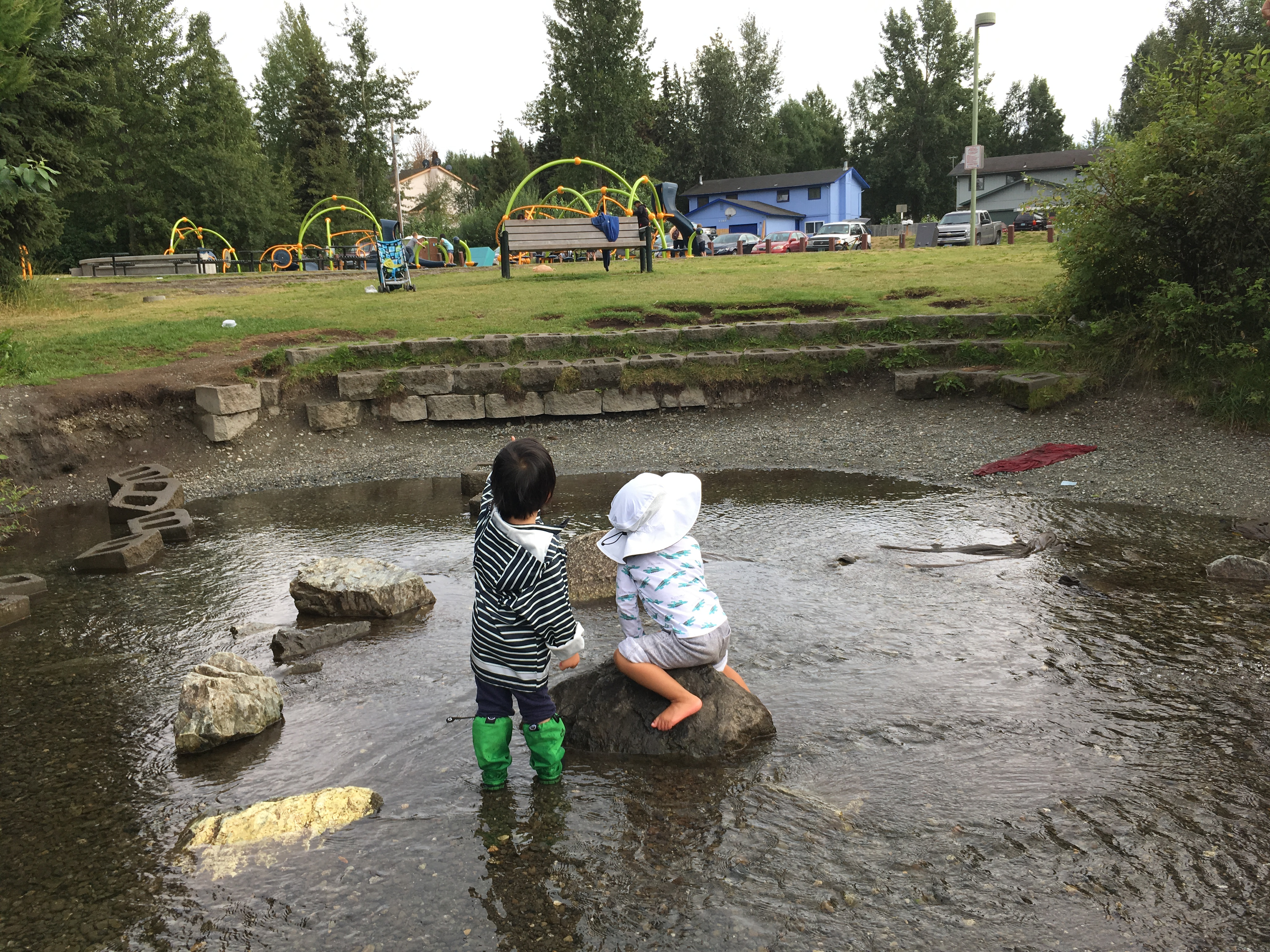 Two toddlers play together in a creek next to a playground