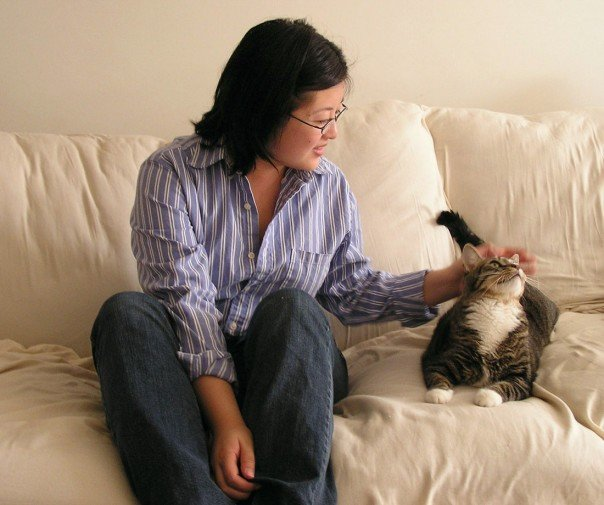 Asian woman in blue striped button-down shirt and jeans, petting a grey tabby cat