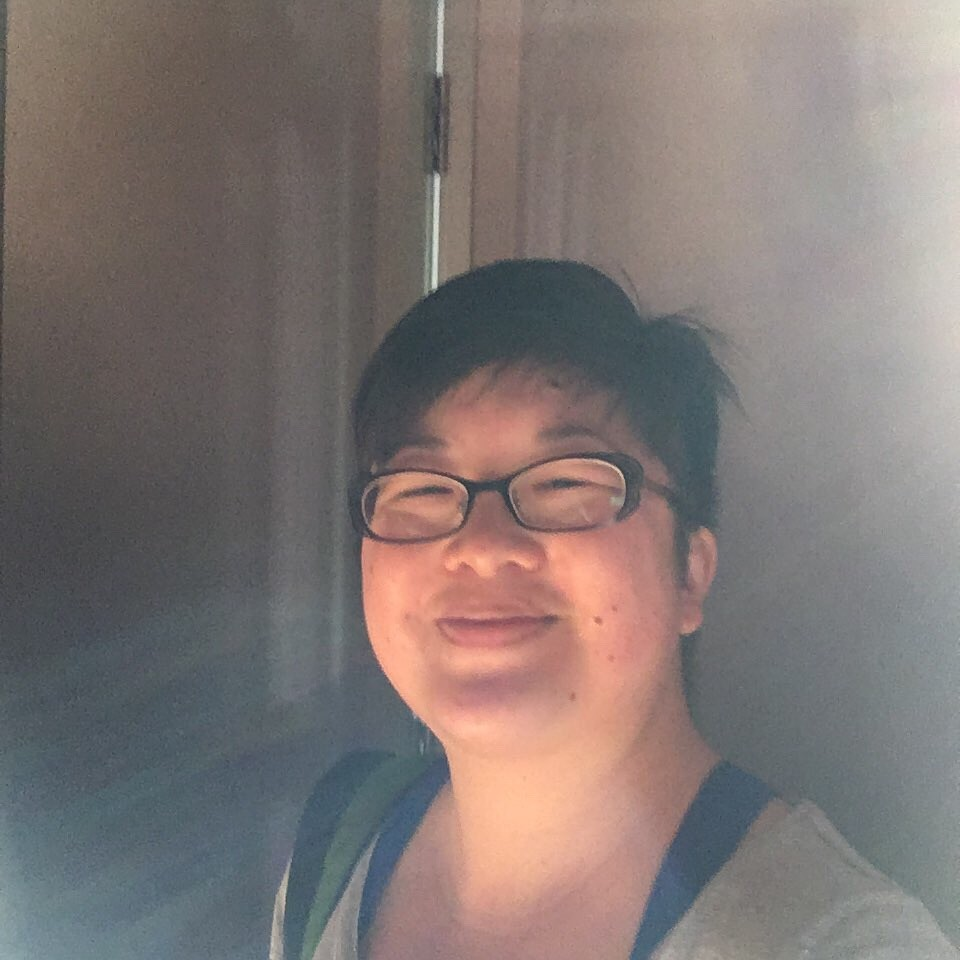 beaming short-haired Asian woman with glasses