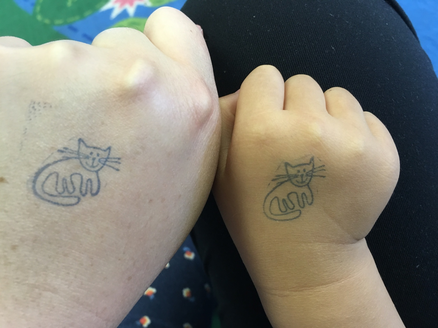 An adult and a kid's hand next to each other, both with a cat hand stamp