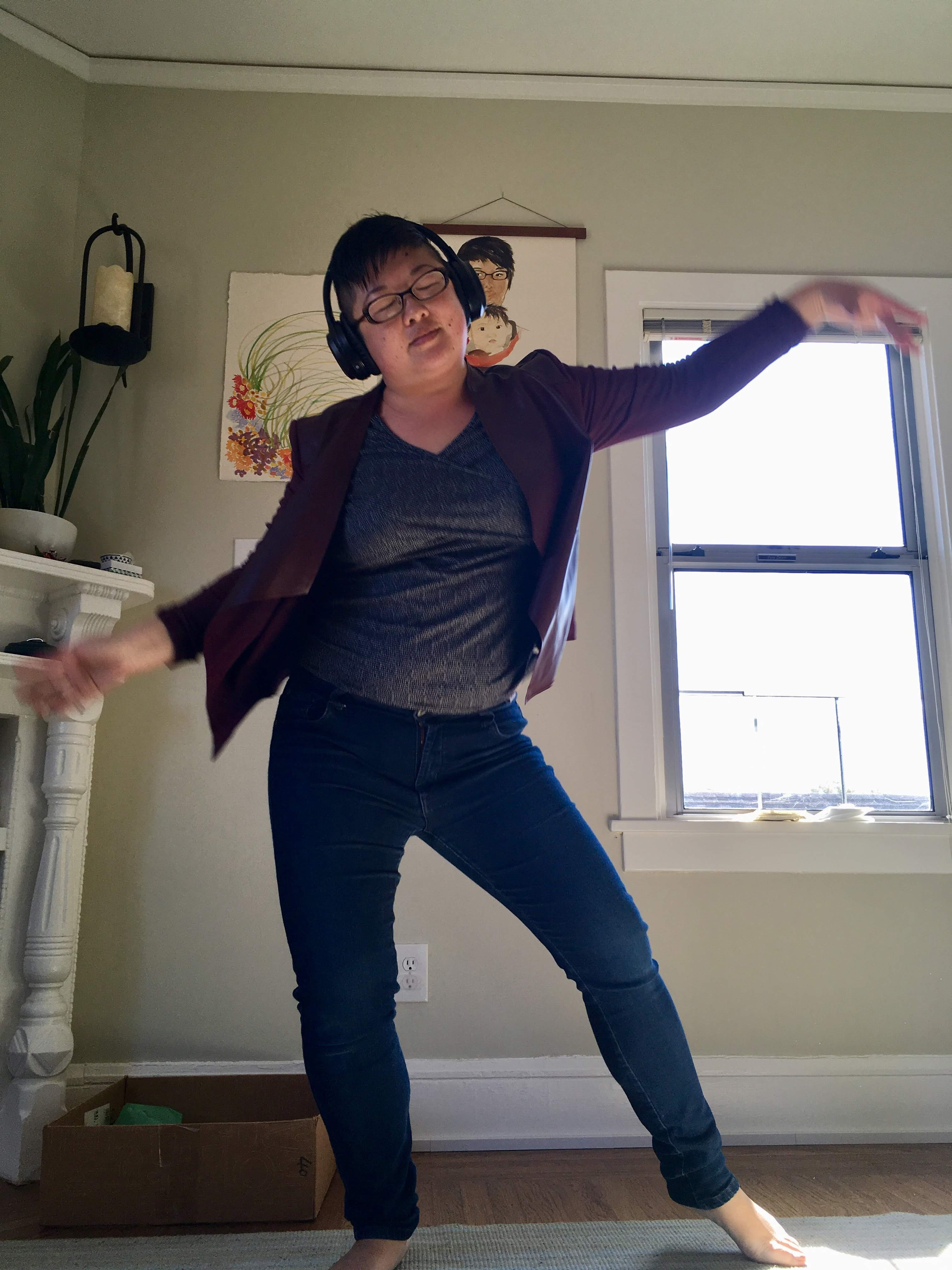 Short-haired, glasses-and-headphones-wearing Asian woman dances indoors