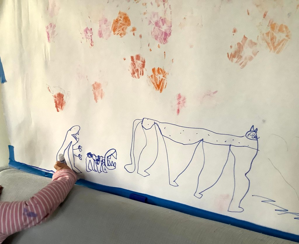 A small child draws fantastical creatures