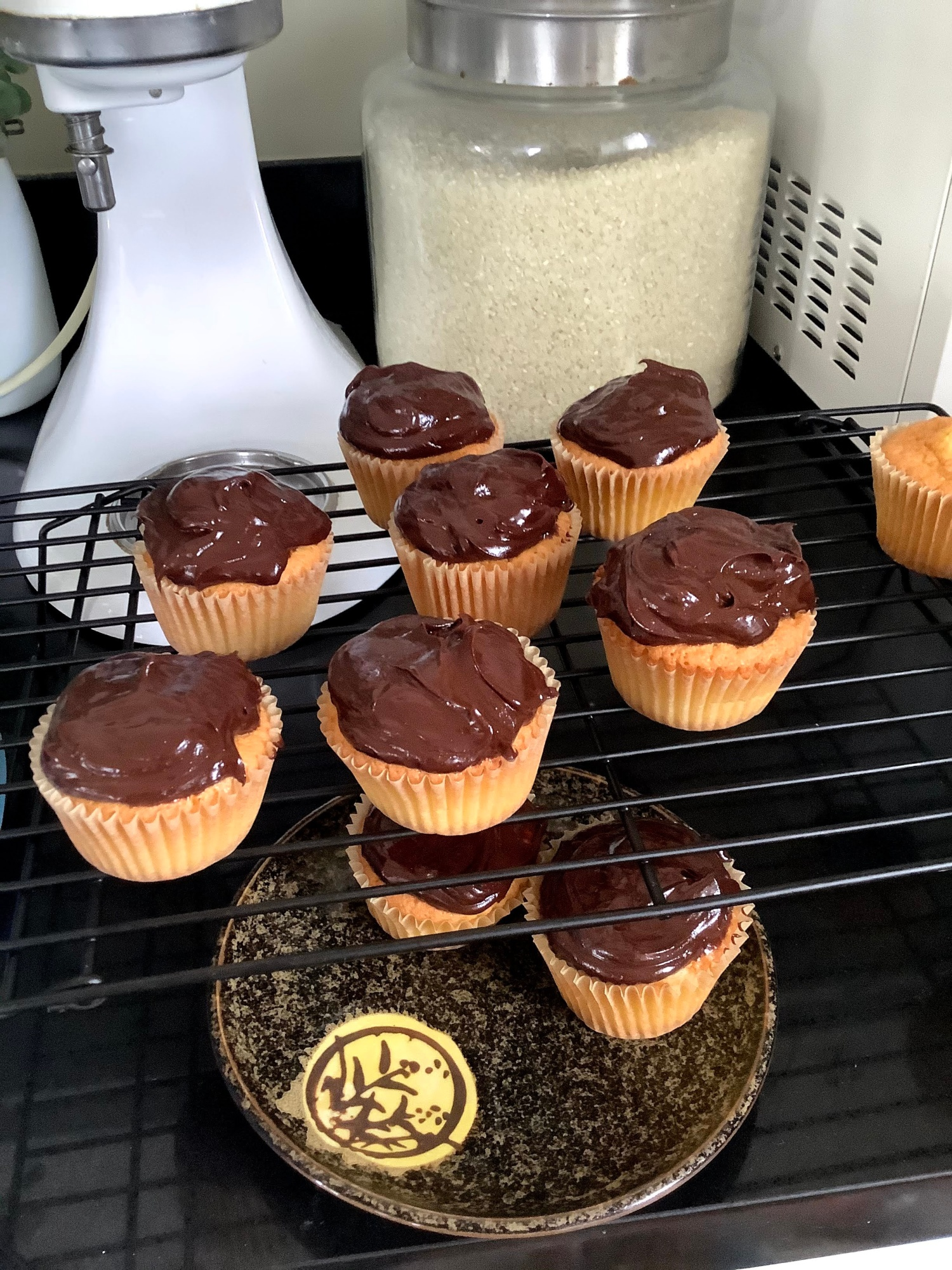 Yellow cupcakes topped with chocolate ganache, on a rack