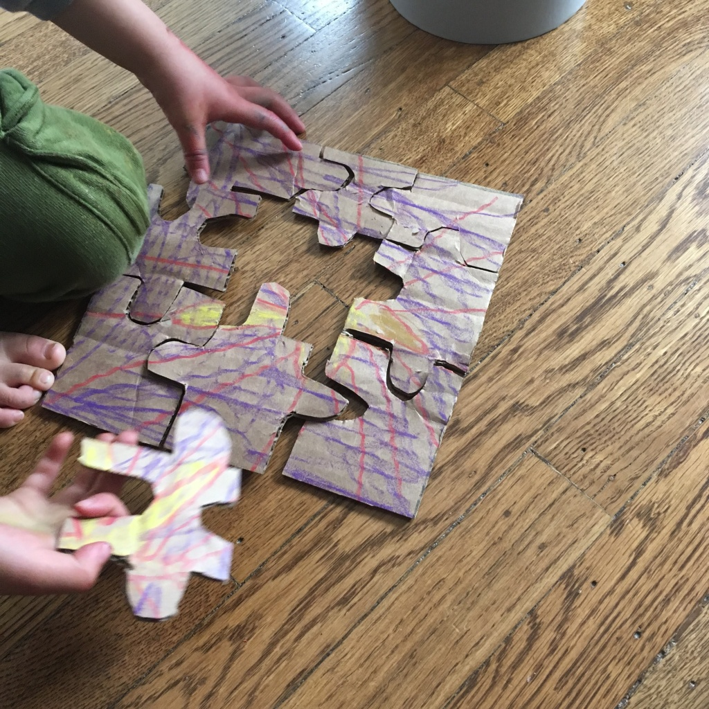 A young child assembles a homemade puzzle made from a crayon drawing on corrugated cardboard.