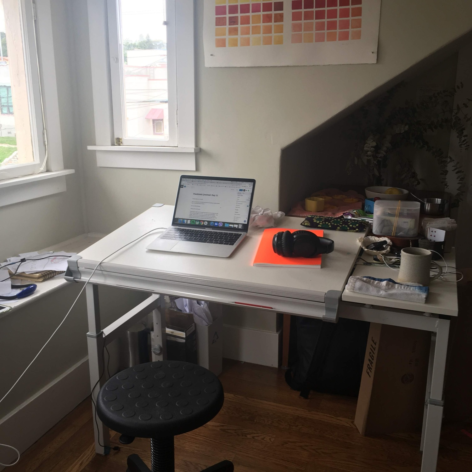 A cluttered drafting table next to a window