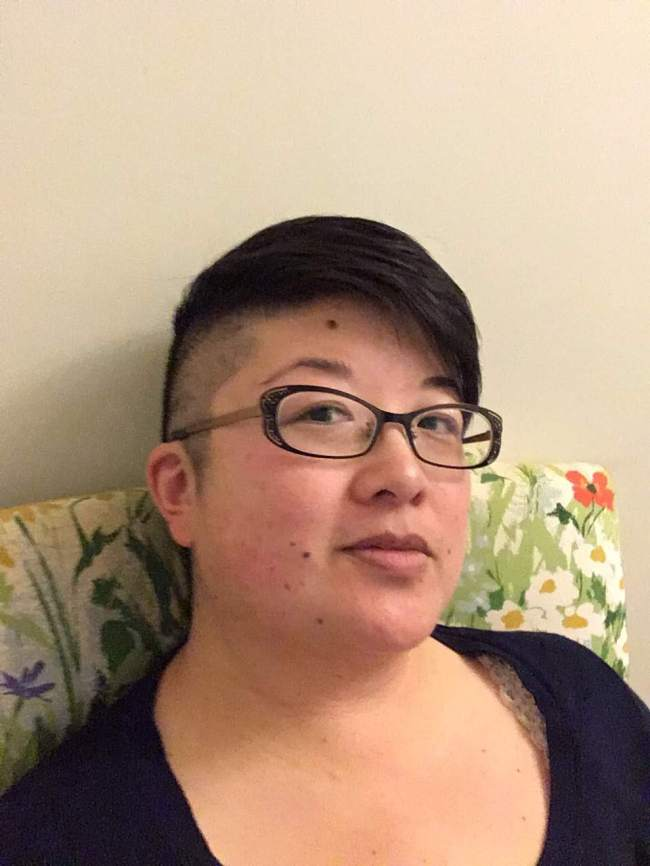 38yo Asian American person with short hair, shaved sides, and black-framed glasses