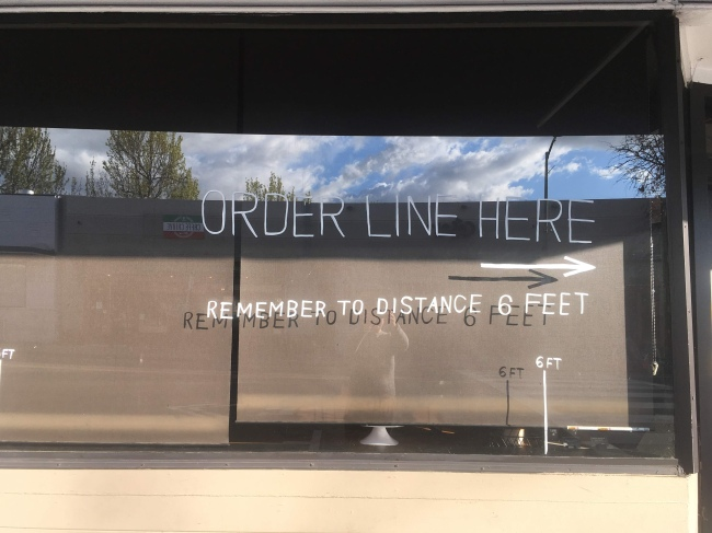 Words painted on a store window requesting customers to socially distance while in line