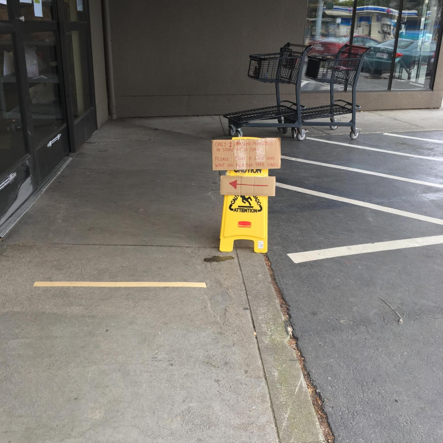 Social-distancing sign in red marker on cardboard, taped to a yellow CAUTION sign