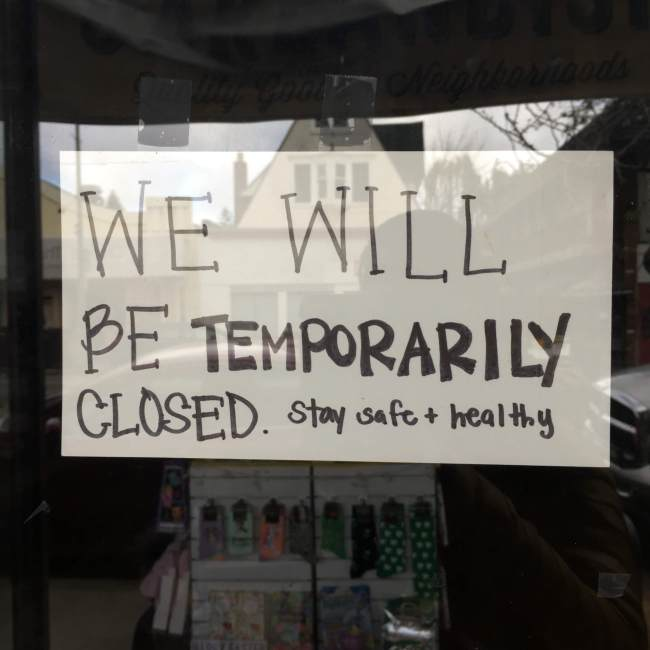 "Hand-lettered ""we will be temporarily closed"" sign on a business door"
