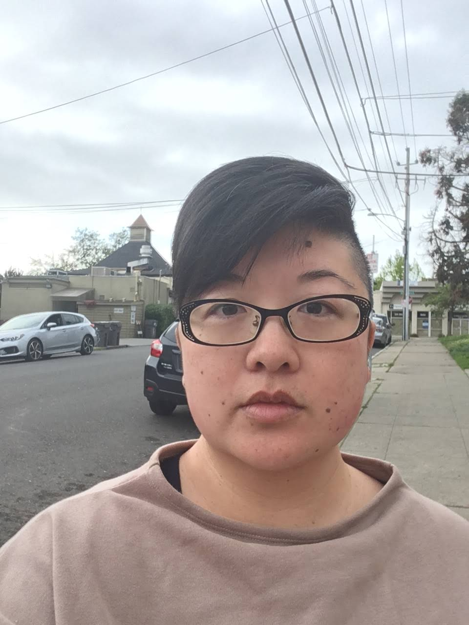 Asian woman with short hair and shaved sides, black glasses, taupe sweatshirt