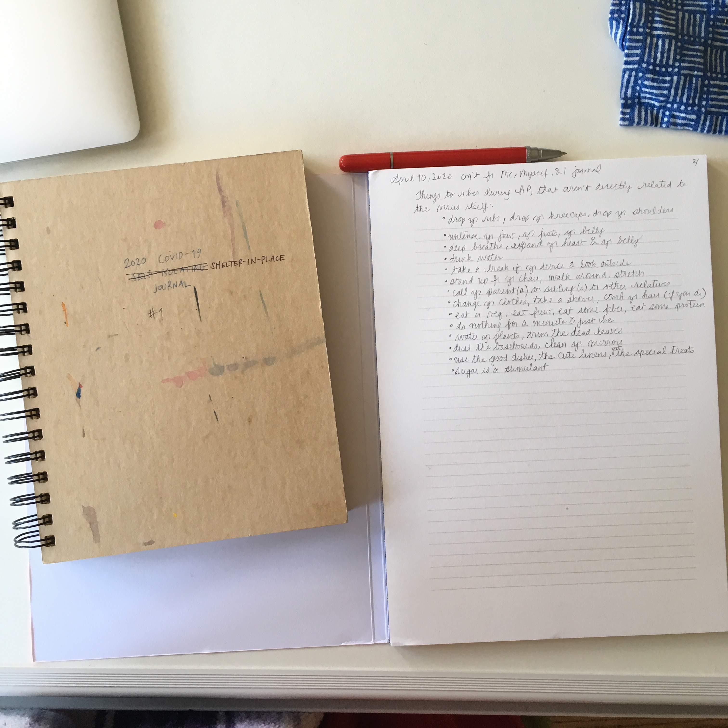 Two notebooks next to each other, one spiral-bound and the other not