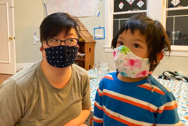 Short-haired East Asian American parent and young child with masks