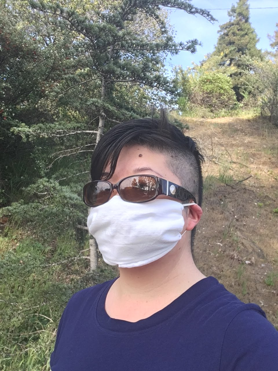 Short-haired Asian woman wearing sunglasses and a face mask improvised from a white hankie
