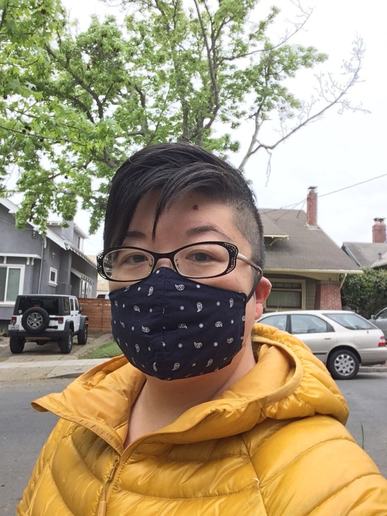 Asian American woman in short hair and glasses, wearing a navy blue face mask