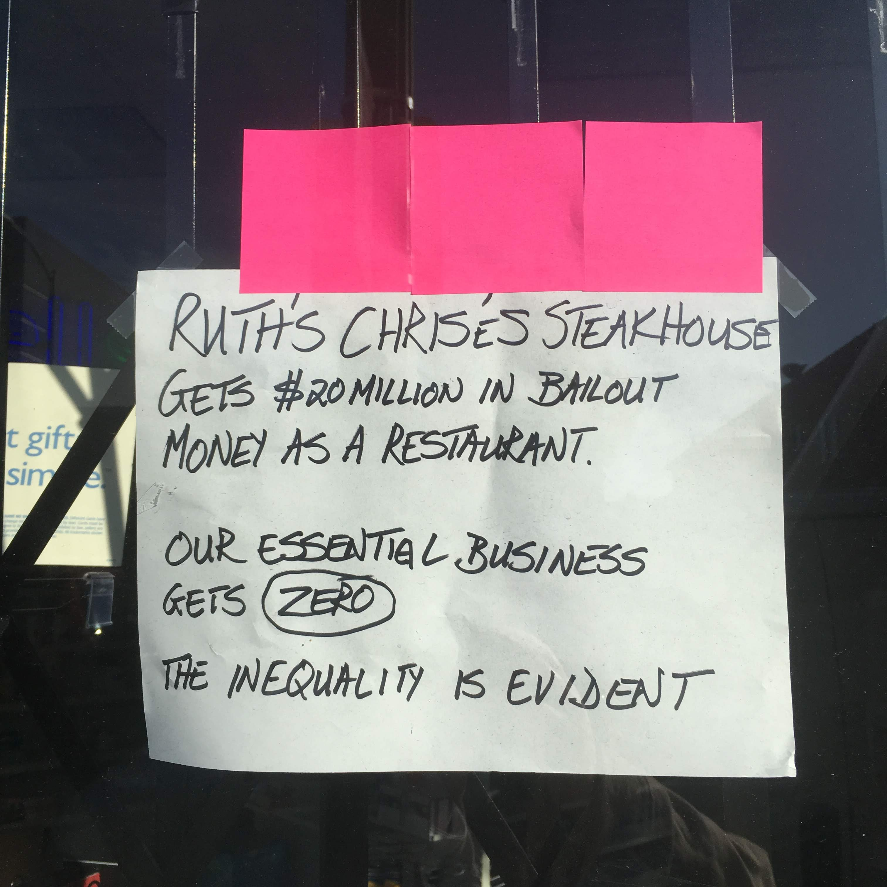 Hand-written sign in the window of Wellspring Pharmacy, Oakland, commenting on their business receiving no bailout money